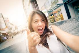 Premium Photo | Happy asian woman excited with thumb up taking selfie in  city street