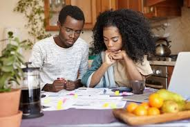 Free Photo | Young african couple doing paperwork together, sitting at  kitchen table with lots of papers