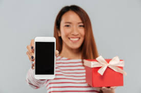 Free Photo | Happy young asian woman showing display of phone holding gift.
